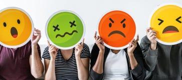 Różnorodni ludzie trzyma różnorodnych emoticons Zdjęcie Royalty Free