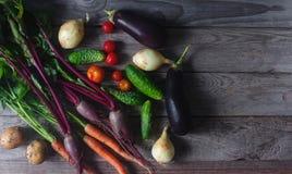 Różnorodni organicznie warzywa na nieociosanym drewnianym tle, zdrowy styl życia, jesieni żniwo, surowy jedzenie, odgórny widok Fotografia Stock