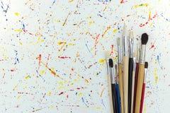 różnorodni paintbrushes na białym papierze z akwareli kroplami Obrazy Royalty Free