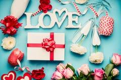 Różnorodni powitanie miłości przedmioty: butelka szampan, prezenta pudełko, faborek, kwiaty, łęk, szkła i serca na bławym desktop obrazy stock