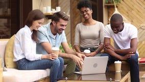 Różnorodni przyjaciele ma zabawę z laptopu obsiadaniem na kawiarnia tarasie zbiory wideo