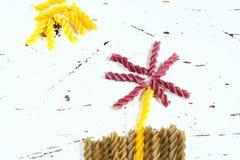 Różnorodni rodzaje barwiony surowy makaron na białym tle, odgórnym widoku w postaci kwiatów poly i słońca od jedzenia, Fotografia Royalty Free
