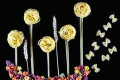 Różnorodni rodzaje barwiony surowy Włoski makaron, banatka wywodzą się na czarnym tle, odgórny widok, w postaci kwiatów poly i bu Obraz Stock