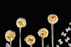 Różnorodni rodzaje barwiony surowy Włoski makaron, chili pieprz na czarnym tle, odgórny widok w postaci kwiatów poly i butterf, Zdjęcie Stock