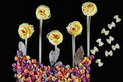 Różnorodni rodzaje barwiony surowy Włoski makaron, chili pieprz na czarnym tle, odgórny widok w postaci kwiatów poly i butterf, Zdjęcia Stock