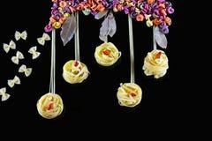 Różnorodni rodzaje barwiony surowy Włoski makaron na czarnym tle, odgórnym widoku w postaci kwiatów poly i motyli od jedzenia, Zdjęcie Stock