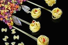 Różnorodni rodzaje barwiony surowy Włoski makaron na czarnym tle, odgórnym widoku w postaci kwiatów poly i motyli od jedzenia, Obrazy Royalty Free