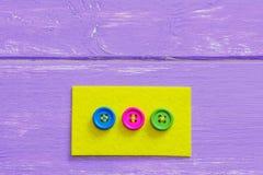 Różnorodni sposoby szyć guziki filc Żółty mieszkanie czuł z jaskrawymi guzikami na drewnianym tle z kopii przestrzenią szy fotografia stock
