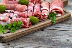 Różnorodni surowi mięsa na porci wsiadają z nieociosanym tłem zdjęcie stock