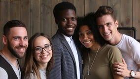Różnorodni szczęśliwi młodzi ludzie pozuje robić fotografii, patrzeje kamerę zbiory