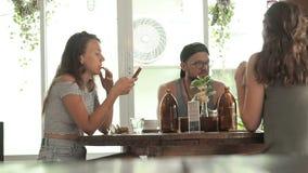 Różnorodni ucznie siedzi wokoło stołu w kawiarni i opowiada coś Spotykać życzliwej firmy przy stołem w kawiarni zdjęcie wideo