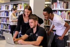 Różnorodni ucznie w szkoła wyższa kampusu bibliotece obraz stock