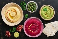 Różnorodność barwiony hummus w talerzu, granatowu, oliwkach i pita na ciemnym tle, Odgórny widok, mieszkanie nieatutowy obraz stock