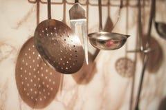 Różnorodność kuchenni naczynia wieszają przeciw tłu marmurowa fartuch ściana zdjęcia stock