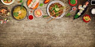 Różnorodny azjatykci posiłki na nieociosanym tle, odgórny widok, miejsce dla teksta Zdjęcia Stock