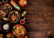 Różnorodny azjatykci posiłki na nieociosanym tle, odgórny widok, miejsce dla teksta Obraz Stock
