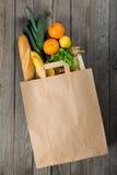 Różnorodny jedzenie w papierowej torbie na drewnianym tle obrazy royalty free