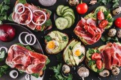 Różnorodny kanapki i bruschetta z prosciutto, smażący przepiórki jajko, avocado, ogórek, pomidory obrazy stock