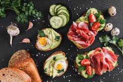Różnorodny kanapki i bruschetta z prosciutto, smażącym przepiórki jajkiem, avocado, ogórkiem, pomidorami, pikantność i zieleniami zdjęcia stock