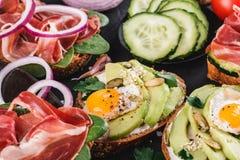 Różnorodny kanapki i bruschetta z prosciutto, smażącym przepiórki jajkiem, avocado, ogórkiem, pomidorami, pikantność i zieleniami obrazy royalty free