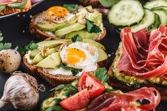 Różnorodny kanapki i bruschetta z prosciutto, smażącym przepiórki jajkiem, avocado, ogórkiem, pomidorami, pikantność i zieleniami obraz royalty free