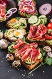 Różnorodny kanapki i bruschetta z prosciutto, smażącym przepiórki jajkiem, avocado, ogórkiem, pomidorami, pikantność i zieleniami fotografia stock