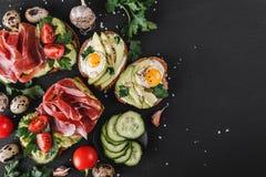 Różnorodny kanapki i bruschetta z prosciutto, smażącym przepiórki jajkiem, avocado, ogórkiem, pomidorami, pikantność i zieleniami obraz stock