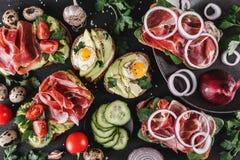 Różnorodny kanapki i bruschetta z prosciutto, smażącym przepiórki jajkiem, avocado, ogórkiem, pomidorami, pikantność i zieleniami zdjęcia royalty free