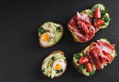 Różnorodny kanapki i bruschetta z prosciutto, smażącym przepiórki jajkiem, avocado, ogórkiem, pomidorami, pikantność i zieleniami fotografia royalty free