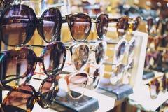 Różnorodny kolorowi słońc szkła wiesza w sklepie zdjęcia stock