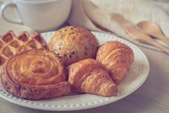 Różnorodny piec chleb na talerzu i filiżance zdjęcie stock