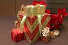 Różnorodny rozmiar prezentów pudełek sterta z suchą sosną konusuje i sztuczna poinsecja kwitnie dla Bożenarodzeniowych dekoracji obraz royalty free