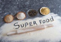 Różnorodny Superfoods i wpisowego ` Super karmowy ` na popielatym stole Tło pieczenie z naturalnymi additives mąka fotografia stock