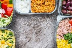 Różnorodnych Zdrowych warzyw lunchu sałatkowi pudełka w plastikowych pakunkach na szarość drylują tło, odgórny widok, rama Obrazy Stock