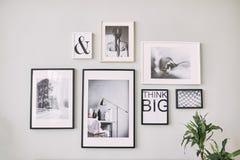 Różny rozmiar obramiać fotografie wiesza na szarości ścianie zdjęcie stock