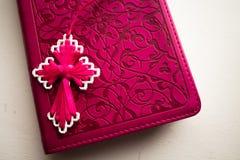 Różowa biblia z handmade menchiami krzyżuje na nim Obraz Stock