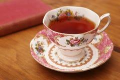 Różowa Herbaciana filiżanka i antyk książka obraz stock