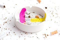 Różowa i żółta pomoc sticked na białym ashtray z zniszczonym cigarrette wokoło Obraz Stock