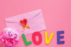 Różowa koperta z czerwonym sercem, kwiatu bukietem i miłości słowem na pi, zdjęcia royalty free