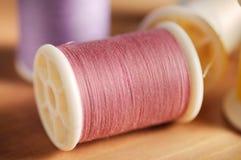 Różowa nić na drewno stołu płytkiej głębii pole (miękka ostrość) Zdjęcie Stock