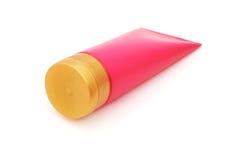 Różowa plastikowa tubka z zamkniętym żółtym trzepnięcie wierzchołka deklem Fotografia Stock