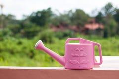 Różowa podlewanie puszka z zielenią zamazywał natury tło Zdjęcie Stock