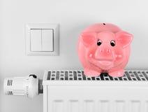 Różowa prosiątko banka oszczędzania elektryczność i grzejni koszty obrazy royalty free