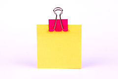 Różowa segregator klamerka na pustym koloru żółtego papierze Obrazy Royalty Free