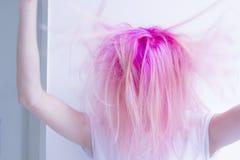 Różowa włosiana kobieta jest otynkowaniem jej włosy, czuć szalony obrazy royalty free