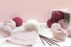 Różowa wełny przędza w zwitkach z ciepłym kapeluszem Zdjęcia Stock