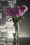 Różowe peonie w szklanej wazie na błyszczącym czerń stole Fotografia Royalty Free