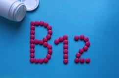 Różowe round pigułki wykładali z listem B12 zdjęcia stock