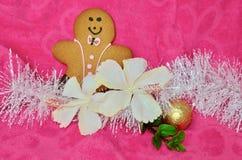Różowego Bożenarodzeniowego tła piernikowego mężczyzna poślubnika szczęśliwi biali kwiaty i biały tinsle Fotografia Royalty Free