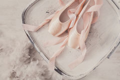 Różowi baletniczy pointe buty, piórko na białym drewnianym tle i Fotografia Stock